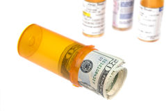 Cash in pill bottle Stock Photos
