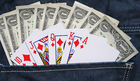 Cash and playing in denim jeans pocket royalty free stock image