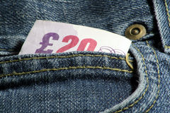 Cash in pockets. British 20 pound note in jeans pocket stock photos