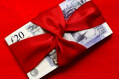 Cash prize. Stack of english twenty pounds notes tied with red ribbon isolated on red background Royalty Free Stock Photos