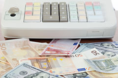 Cash register and different paper currencies Stock Images