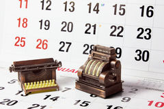 Cash Register and Typewriter on Calendar Pages Royalty Free Stock Photography