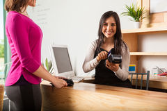 Cash register worker swiping a card. Cute Latin young women working at a cash register and swiping the credit card of a customer Royalty Free Stock Photo
