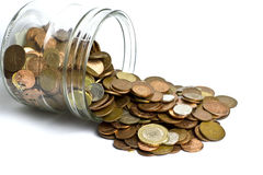 Cash Spilling out from Jar. Coins spilling out of cash  jar isolated on white background Stock Images