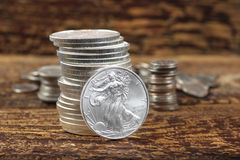 Cash Stash. Stack of mint condition Liberty Silver dollars on wood with stacks of other coins in the background Stock Photo