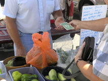 Cash Transaction. Vendor at farmers market recieves cash to add to the wad already in pocket Royalty Free Stock Photography