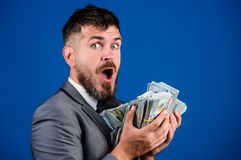 Cash transaction business. Man happy winner rich hold pile of dollar banknotes blue background. Easy cash loans. Businessman got cash money. Win lottery stock image