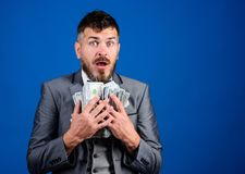 Cash transaction business. Man happy winner rich hold pile of dollar banknotes blue background. Win lottery concept. Easy cash loans. Businessman got cash stock image