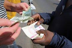 Cash. Two men changing Zimbabwe Dollar Royalty Free Stock Photos