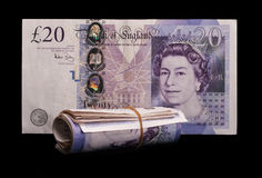 Cash - wad of UK sterling notes. A single note and a bundle of more, fastened by an elastic band. Over black Royalty Free Stock Images