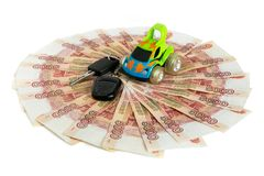 Cash on white background. Toy car and car keys on the money. Bills 5 thousand rubles, spread out like a fan stock photo