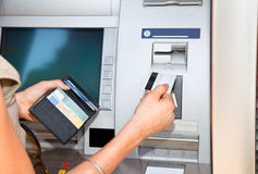 Cash withdrawal with card Visa. Cash withdrawal. Woman's hand inserting plastic card Visa into the ATM Royalty Free Stock Photography