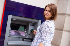 Cash withdrawal. Young woman at the cash machine Royalty Free Stock Image