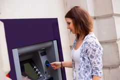Cash withdrawal. Young woman at the cash machine Stock Photos