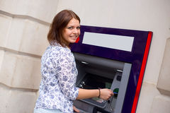 Cash withdrawal. Young woman at the cash machine Royalty Free Stock Photos