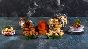 Cashew almonds spill out of transparent cans, dried apricots lie between them royalty free stock photography