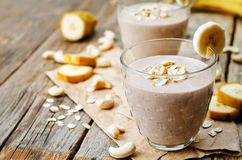 Cashew banana cocoa oats smoothie. On a dark wood background. the toning. selective focus royalty free stock image