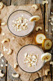 Cashew banana cocoa oats smoothie. On a dark wood background. the toning. selective focus stock photo