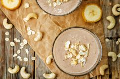 Cashew banana cocoa oats smoothie on a wood background. The toning.selective focus stock image