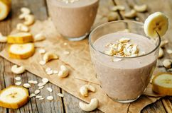 Cashew banana cocoa oats smoothie on a wood background. The toning.selective focus stock photo