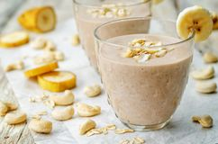 Cashew banana cocoa oats smoothie on a wood background. The toning.selective focus royalty free stock photos