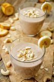 Cashew banana cocoa oats smoothie on a wood background. The toning.selective focus stock photography
