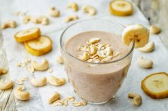 Cashew banana cocoa oats smoothie on a wood background. The toning.selective focus stock images