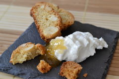 Cashew biscotti with dip. Cashew biscotti with a dip of goats cheese and honey on slate plate as an unusual dessert Stock Image