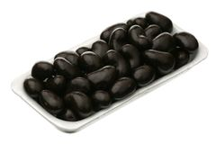 Cashew in chocolate glaze. In the plastic container stock photos