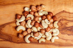 Cashew and hazelnut on wooden background. Cashews and hazelnut on natural wooden brown background Stock Images
