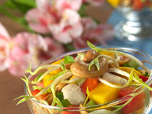 Cashew Nut and Bean Sprout on Salad. Fresh Asian salad with chicken, mango, cucumber, bean sprouts, red bell pepper and peanuts in glass bowl with inca lily in Stock Photo