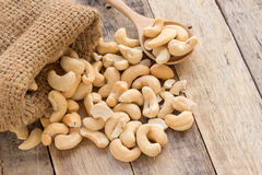 Cashew nut in sack bag on wood table Stock Photo