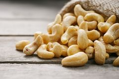 Cashew nuts in burlap bag on wooden gray background . Healthy food. Cashew nuts in burlap bag on wooden background . Healthy food. Indian nut, Anacardium western royalty free stock photo