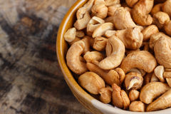 Cashew nuts. In container on wood background Stock Image