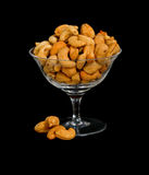 Cashew Nuts in crystal bowl. Fresh salted cashew nuts in a crystal bowl on black background Royalty Free Stock Images