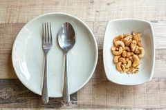 Cashew nuts on the plate. With catering sets Stock Photo