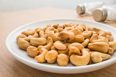 Cashew nuts on plate and salt shaker Royalty Free Stock Photography