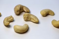 Cashew Nuts on a White Table - Closeup. Natural, organic cashew nuts in a closeup photo. Photographed on top of a white table. Delicious and healthy nuts full of stock photos