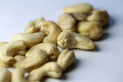 Cashew Nuts on a White Table - Closeup. Natural, organic cashew nuts in a closeup photo. Photographed on top of a white table. Delicious and healthy nuts full of royalty free stock images