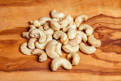 Cashew nuts on wooden background. Cashews nuts on natural wooden brown background Stock Image