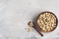 Cashew nuts in a wooden bowl, top view, copy space, food background. Healthy vegetarian food concept.