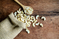 Cashew nuts with wooden spoon on old wood textured. Background Stock Images