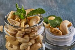 Cashew in a transparent jar with sheets of mint on top stock image