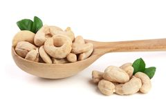 Cashew in a wooden spoon with leaf isolated on white background Royalty Free Stock Photos