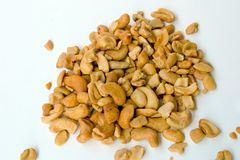 Cashews. Cashew nuts spilled from their container onto a white card royalty free stock image