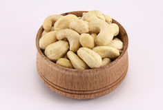 Cashews in a round wooden form. On a white background Royalty Free Stock Photo