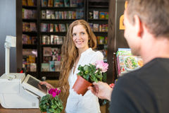 Cashier in flower shop serving customer Stock Photo