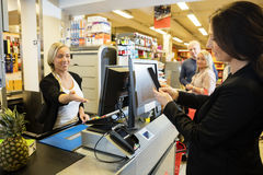 Cashier Gesturing While Customer Doing NFC Payment. Smiling female cashier gesturing while customer doing NFC payment in grocery store Royalty Free Stock Photos