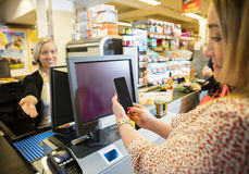 Cashier Gesturing While Female Customer Doing NFC Payment. Smiling cashier gesturing while female customer doing NFC payment in grocery store Stock Image