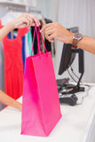 Cashier giving customer a pink shopping bag Royalty Free Stock Photos
